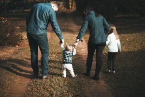 Rodzice z dziećmi idący trzymając się za ręce.