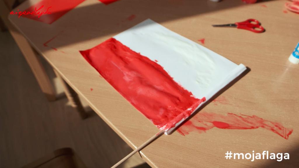 pomalowana farbkami mała flaga schnie na umazanym stoliku