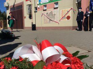 Widok z dołu. Na pierwszym planie wiązanka biało-czerwonych kwiatów. Dalej wójt gminy Jakubów przemawia przed tablicami pamiątkowymi umieszczonymi na ścianie budynku. Na tablicach zawieszone są biało-czerwone wstęgi. Obok strażacy ze sztandarem.