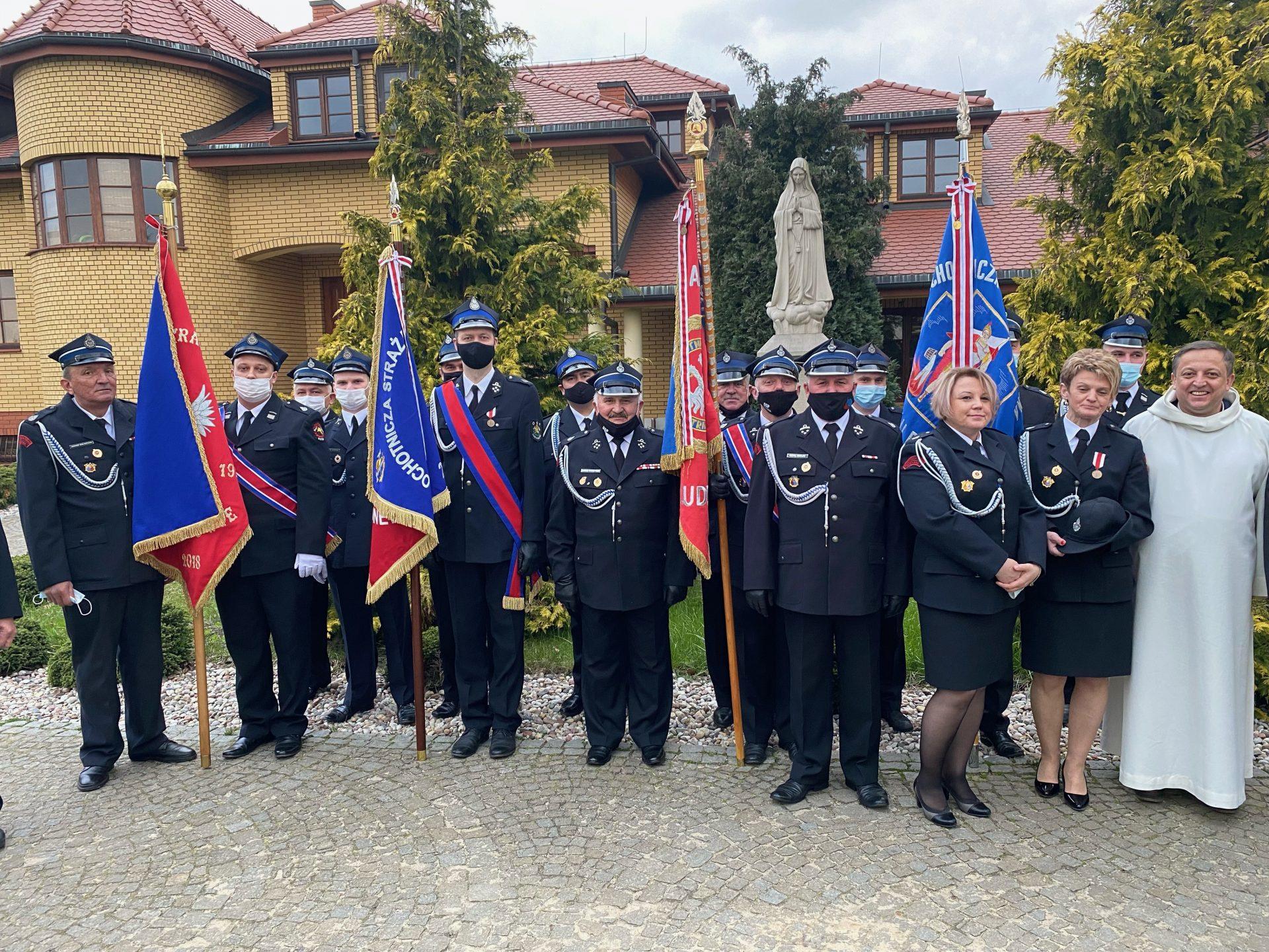 Zdjęcie przedstawia poczty sztandarowe Straży z terenu Gminy Jakubów wraz z Proboszczem Parafii Mistów - Ojcem Marcinem Borządkiem.